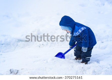 Cute baby boy playing with snow toy shovel in winter outdoor
