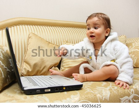 Cute baby boy pointing with the finger on laptop - stock photo