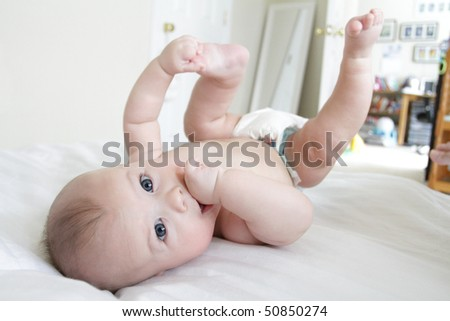 Cute baby boy rolling on bed and playing