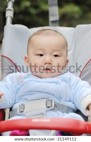 cute baby boy sit in  baby carriage - stock photo