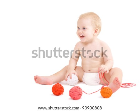 Cute baby boy sits on a floor and plays with clews - stock photo