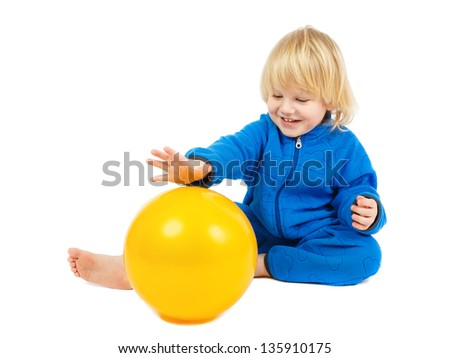 Cute baby boy sits on a floor and plays with yellow ball - stock photo