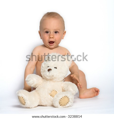 Cute baby boy sits on the floor with his favorite stuffed animal, a white teddy bear. - stock photo