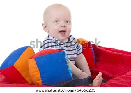 Cute baby boy sits with fabric blocks on bean bag chair - stock photo