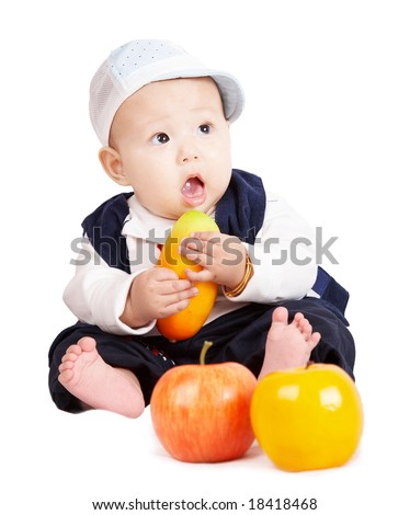 cute baby boy sitting and holding fruit - stock photo