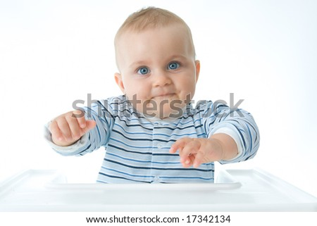cute baby boy sitting in a high chair and making faces - stock photo