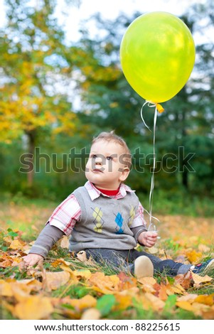 cute baby boy sitting in autumn leaves holding balloon - stock photo