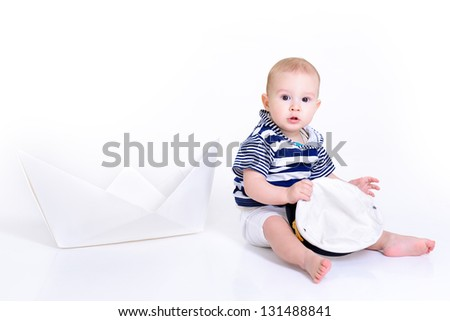 cute baby boy sitting in striped vest with ship of paper and captain cap - sailor in future, over white background - stock photo