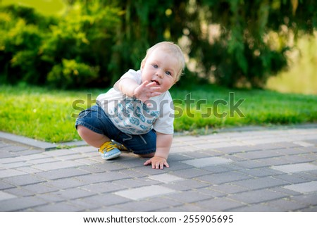 cute baby boy sitting in the spring park happy mother holds out her hand - stock photo