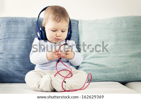 Cute baby boy sitting on sofa and listening music at headphones while  looking at iphone. - stock photo