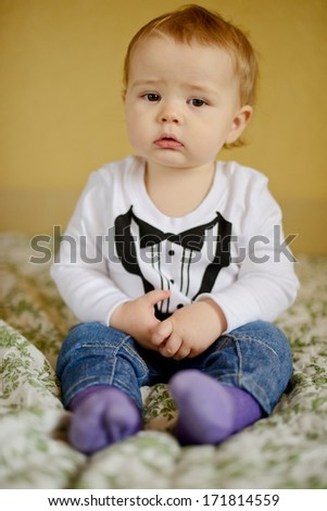 cute baby boy sitting on the sofa (soft selective focus) - stock photo