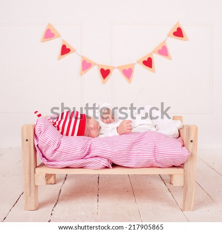 Cute baby boy sleeping on hearts background in white cozy room. Valentines decorations. - stock photo