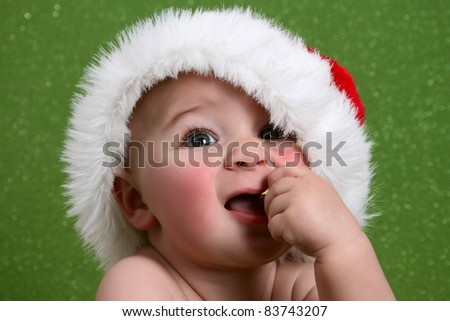 Cute baby boy wearing a christmas hat against green - stock photo
