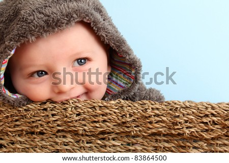 Cute baby boy wearing a fluffy suit in basket - stock photo