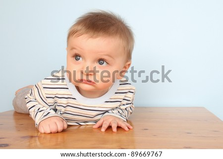 Cute baby boy wearing a striped shirt against blue background - stock photo