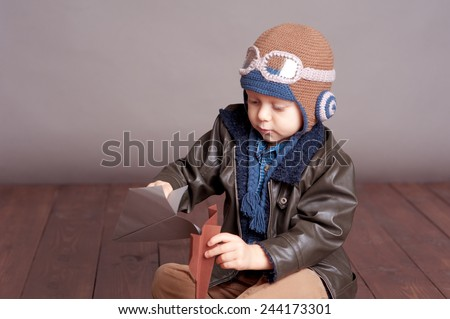 Cute baby boy wearing stylish leather jacket and aviator cap over gray. Playing with paper origami planes in room. Sitting on wooden floor. Childhood. - stock photo