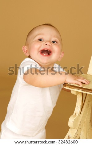Cute Baby Boy with a hugh smile standing next to a bench - stock photo
