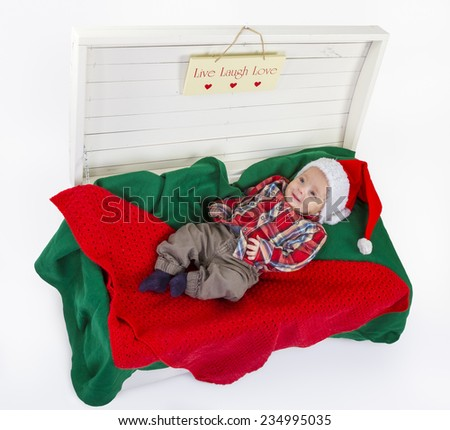 cute baby boy with a santa claus hat in wooden box on white background - stock photo