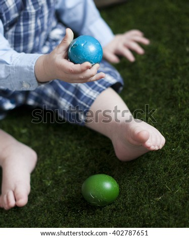 Cute baby boy with Easter eggs on green grass