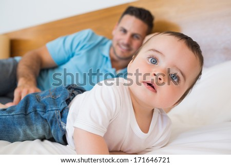Cute baby boy with father in background on bed - stock photo