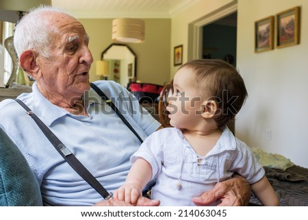 Cute baby boy with great grandfather in a home setting. - stock photo