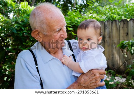 Cute baby boy with great grandfather outdoors. - stock photo