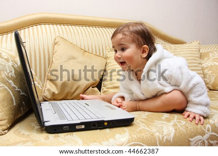 Cute baby boy with laptop on sofa - stock photo