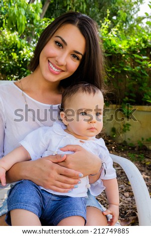 Cute baby boy with pretty young woman outdoors. - stock photo