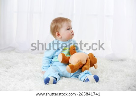 Cute baby boy with teddy bear on carpet, on light background