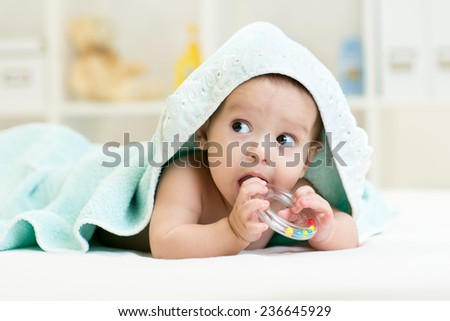 Cute baby boy with teether under towel indoors - stock photo