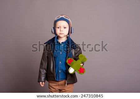 Cute baby boy 3-4 year old wearing stylish leather jacket and aviator cap in room. Playing with knitted toy plane over gray. Looking at camera.  - stock photo