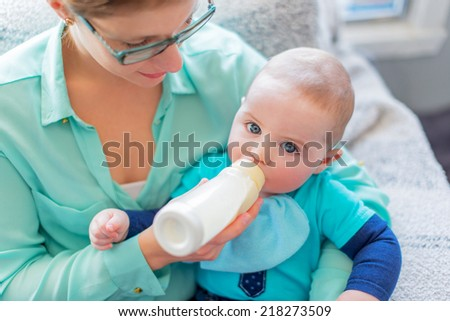 Cute baby brinking from a bottle - stock photo