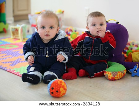 Cute baby brothers playing in the nursery - stock photo