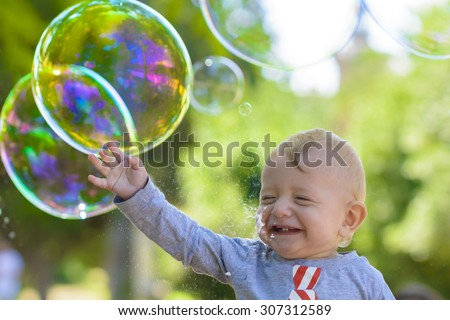 Cute baby catching soap bubbles in a summer day - stock photo