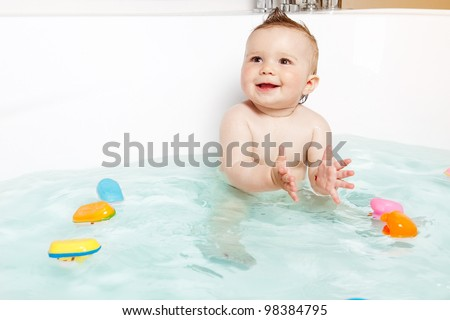 Cute baby clapping hands and smiling while taking a bath - stock photo