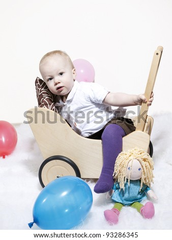 Cute baby climbing into dolls pram - stock photo