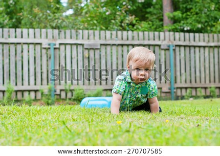 Cute baby crawling in the grass near wooden fence  - stock photo