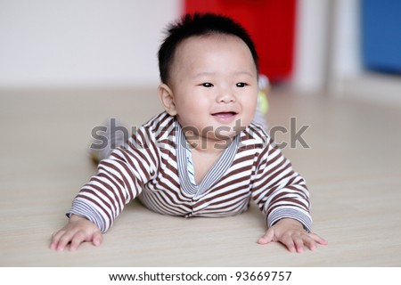 Cute Baby crawling on living room floor with home background, baby is a cute asian infant - stock photo