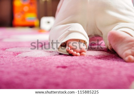 Cute baby crawling on pink carpet. Rear view. Primary focus on baby feet. - stock photo
