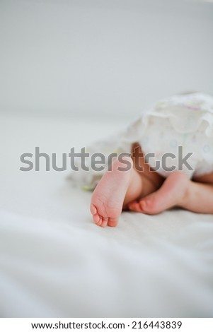 cute baby crawling on the bed. Primary focus on baby feet. - stock photo