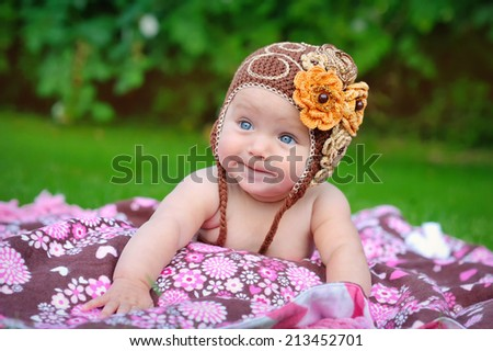 Cute baby crawling outdoors in brown knitted cap - stock photo