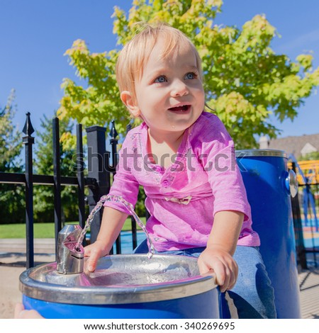 Cute baby drinking from water drinking fountain in summer. Toddler girl first attempts to do adult things. Bright sun, hard shadows. Selective focus on water stream and girls face.