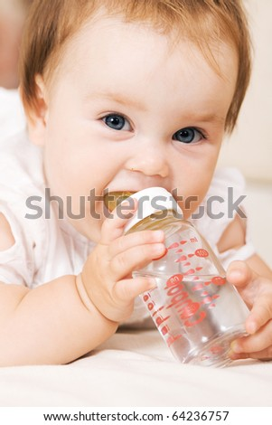 Cute baby drinking water and looking at the camera - stock photo
