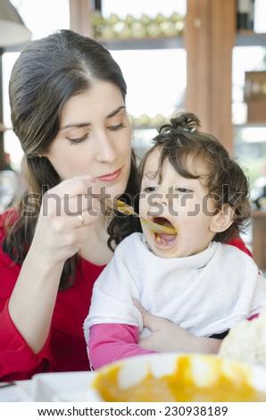Cute baby eating food jar at restaurant - stock photo