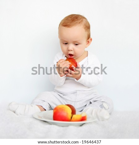cute baby eating fruit - stock photo