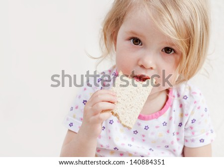 cute baby eats bread on a white background - stock photo