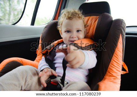 Cute baby  enjoying a road trip in a baby car seat - stock photo