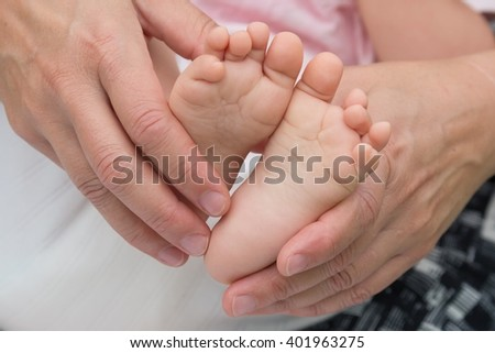 Cute baby feet in her mothers' hands - stock photo