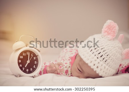 cute baby girl and alarm clock wake up in the morning.