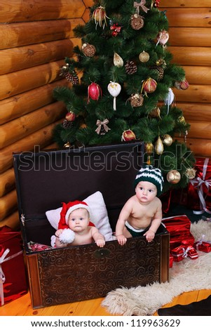 Cute baby girl and baby boy in xmas hats inside large chest - stock photo